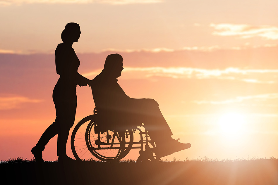 Family Law Act Ontario Personal Injury Lawyers image of a woman pushing an elderly man in a wheelchair, silhouette with a sunset background