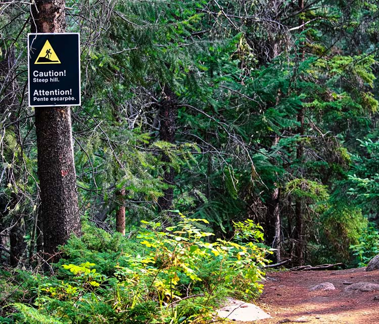 Reybroek Law blog - Municipal Liability - image of a beautiful green trail with a steep decline and signage warning, topic injury in a public park or public trail