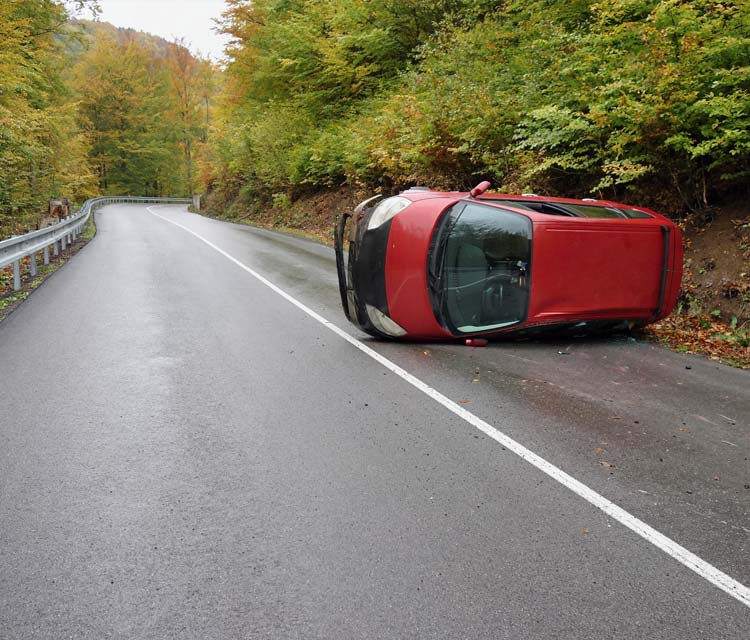 Reybroek Law blog - out of province car accident - image of a red van roll over on a country road out of province