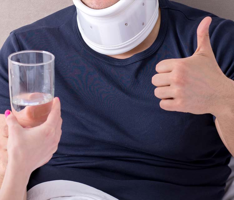 Reybroek Law blog - Attendant Care - image of young man in a neck brace recovering from a car accident being taken care of by his wife